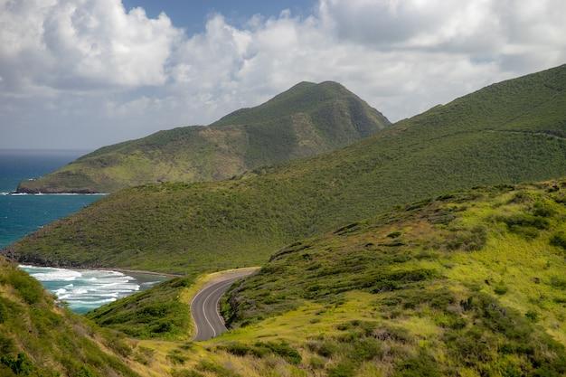 Spektakuläre straße zwischen bergen und blauem meer mit wolken auf hintergrund.