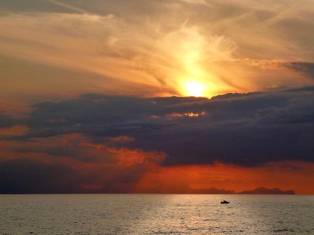 Spektakulärer sonnenuntergang mit rotem himmel und wolken über dem meer von menorca in spanien mit der silhouette eines bootes auf der hellen reflexion der sonne auf dem wasser