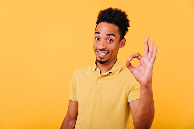 Spektakuläres afrikanisches modell mit trendigem haarschnitt, der mit ok-zeichen aufwirft. innenfoto des verblüfften brünetten schwarzen kerls im sommer-t-shirt.