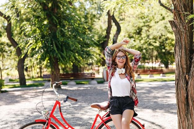 Spektakuläres blondes mädchen, das beim ausruhen im park lacht. debonair gut gekleidete frau, die auf rotem fahrrad sitzt.
