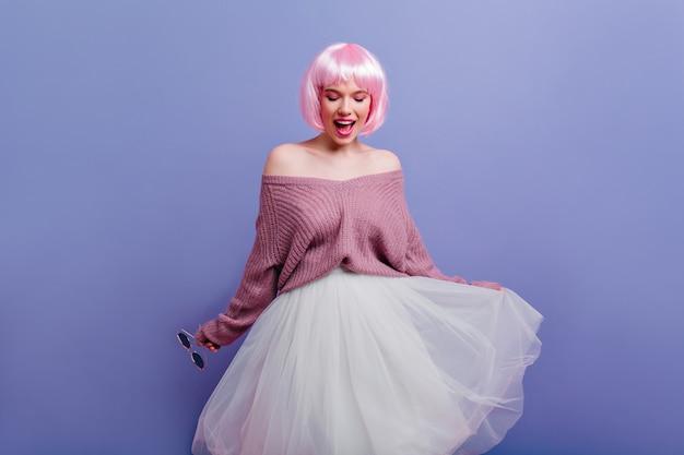 Spektakuläres kaukasisches weibliches modell in der kurzen perücke, die auf lila wand tanzt. innenfoto der bezaubernden weißen dame mit rosa haaren, die im langen üppigen rock aufwerfen.