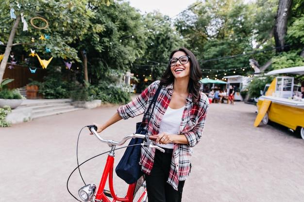Spektakuläres mädchen im lässigen outfit, das im frühling aktive freizeit genießt. weibliches lateinamerikanisches modell in den gläsern, die auf der straße mit fahrrad stehen.