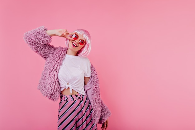 Spektakuläres mädchen in glänzendem rosa peruke, das während des innen-fotoshootings lacht. charmante junge frau in der hellen flauschigen jacke, die positive gefühle ausdrückt
