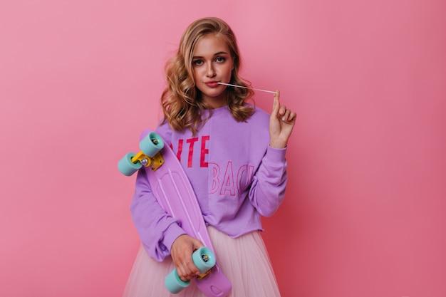 Spektakuläres weißes mädchen mit dem lockigen haar, das auf pastell aufwirft. glamouröses weibliches modell mit buntem skateboard.