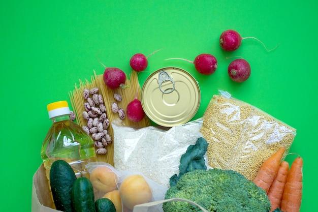 Spende. lebensmittel liefern krisennahrungsmittelvorräte für die quarantäne-isolationszeit auf grünem hintergrund. reis, erbsen, getreide, konserven, öl, gemüse. lebensmittellieferung, coronavirus.