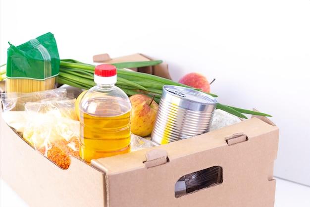 Spende. lebensmittelbox, helfen sie den bedürftigen. spendenbox. karton mit lebensmitteln auf einer weißen oberfläche.