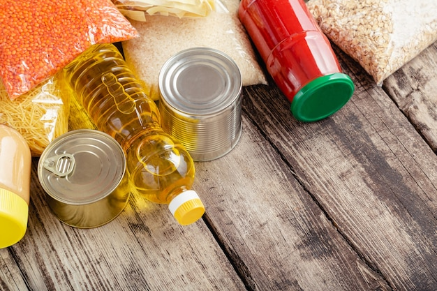 Spenden essen. satz von grundnahrungsmitteln rohes getreide konserven, lebensmittelnudeln auf holztisch. spenden sie hilfe, liefern sie lebensmittel während der covid-quarantäne durch die freiwilligengemeinschaft. nächstenliebe.