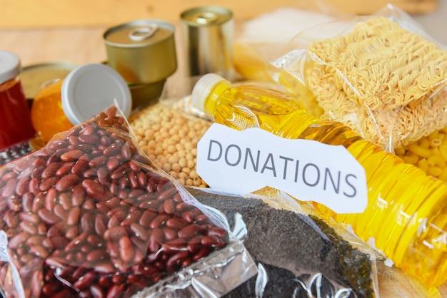 Spenden lebensmittel mit konserven auf holz- / nudelkonserven und trockenfutter nicht verderblich mit erbsenbohnen speiseöl instantnudeln makkaroni, spenden