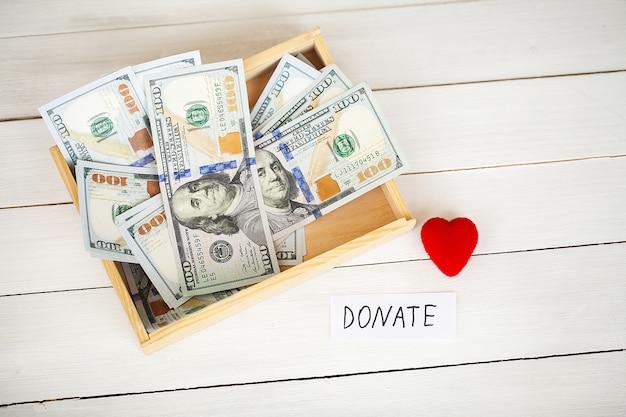 Spenden und wohltätigkeit. spende schachtel mit spenden und herz auf dem weißen.