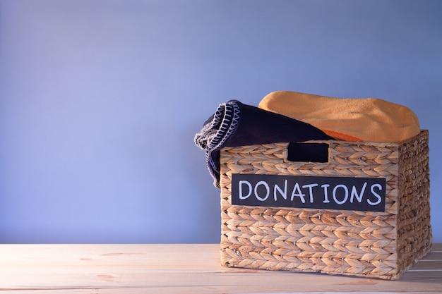 Spendenbox für kleiderspenden auf blauem grund. wohltätigkeits- und spendenkonzept. platz kopieren.