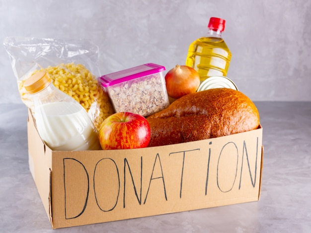 Spendenbox mit essen. lebensmittelgeschäft auf grauem hintergrund. spendenkonzept