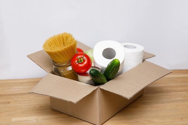 Spendenbox mit essen und toilettenpapier auf dem holzschreibtisch