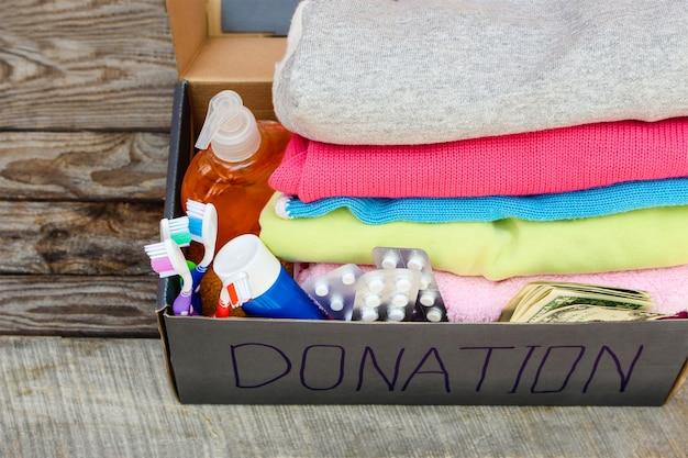 Spendenbox mit kleidung, lebensmitteln und geld.