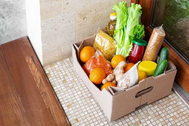 Spendenbox mit lebensmitteln während der covid-quarantäne. food box lieferung vor der haustür in der nähe der tür. kontaktlose soziale hauszustellung, sicheres einkaufen bei coronavirus-pandemie. mahlzeit zum mitnehmen. kurier nach hause lieferung