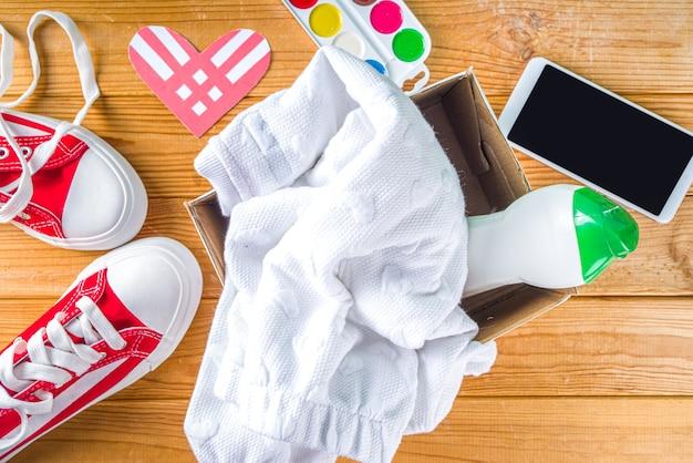 Spendenbox mit verschiedenen geschenkartikeln zum giving tuesday, mit rotem herzlogo. wohltätigkeit. sammeln sie unerwünschte abfallprodukte, übergeben sie es dem konzept der armen bedürftigen menschen. teilnahme an internationalen spendenaktionen.