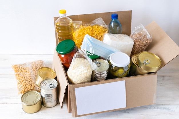 Spendenbox mit verschiedenen lebensmitteln. offener karton mit öl, konserven, müsli und nudeln.