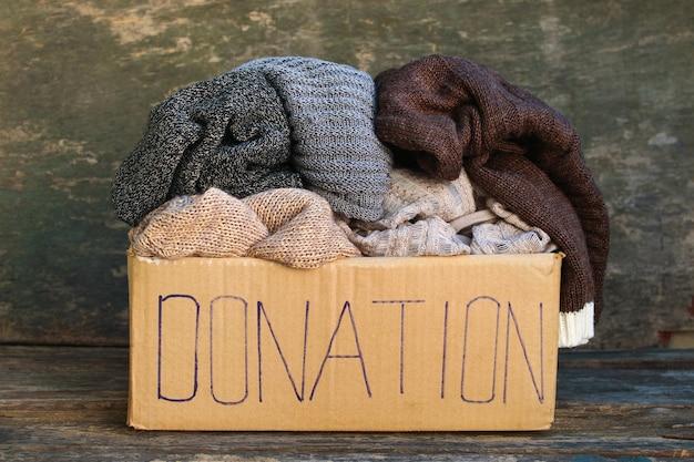 Spendenbox mit warmen dingen auf altem hölzernem hintergrund.