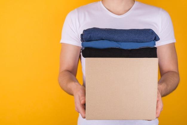 Spendenkonzept. abgeschnittenes nahaufnahmefoto eines mannes, der eine kiste voller kleidung hält, um sie isoliert auf gelbem hintergrund zu spenden