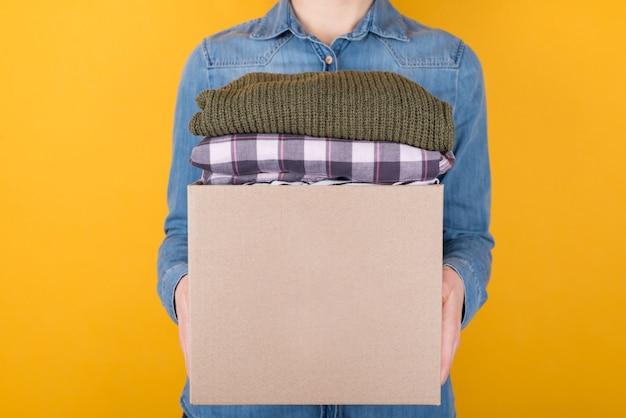 Spendenkonzept. vorderansicht beschnittenes foto einer frau mit einer kiste kleidung zum spenden isoliert auf gelbem hintergrund