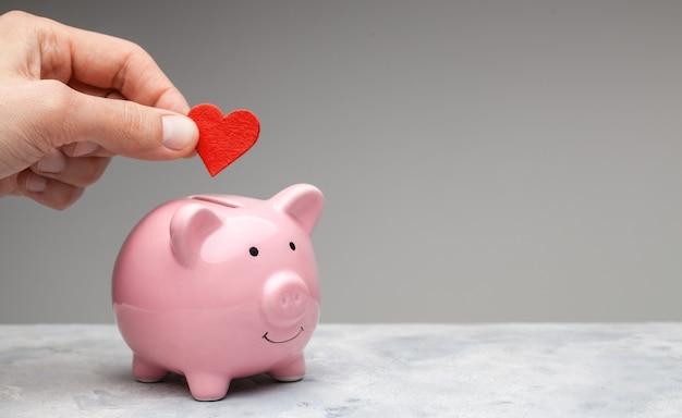 Spender. ein mann hält ein rotes herz in der hand und geht als spende ins sparschwein.