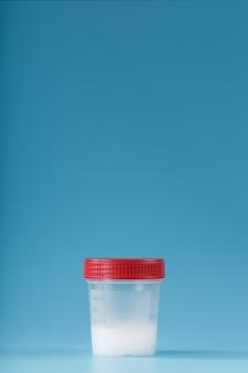Sperma in einem testbehälter mit rotem deckel auf blau