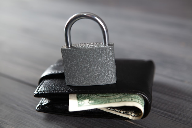 Sperren sie die schwarze brieftasche auf dem holztisch. geldsicherheitskonzept