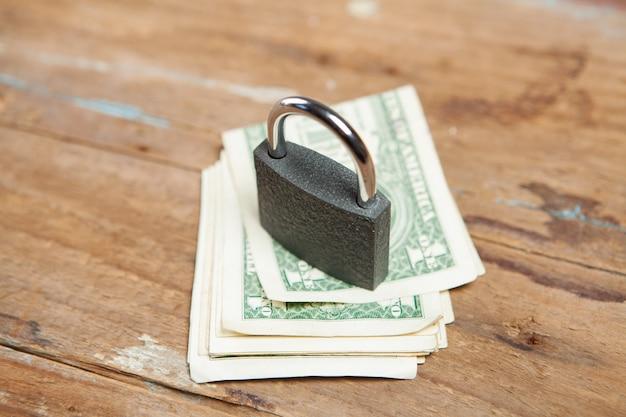 Sperren sie dollarnoten auf einem holztisch
