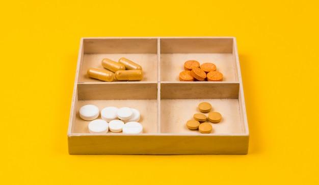 Sperrholzkiste mit vier fächern, die verschiedene medikamente, tabletten, pillen sind. das konzept der erhaltung der gesundheit während der coronavirus-epidemie