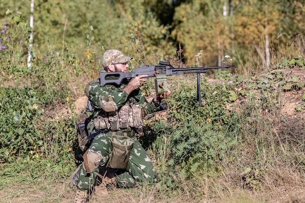 Spezialeinheiten, soldaten-sturmgewehr mit schalldämpfer, optisches visier. hinter deckung im hinterhalt warten