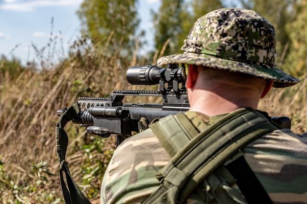 Spezialeinheiten, soldaten-sturmgewehr mit schalldämpfer, optisches visier. hinter der decke wartet ein hinterhalt