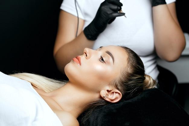 Spezialist für handschuhe, die sich darauf vorbereiten, einer schönen jungen frau im schönheitssalon permanentes brauen-make-up aufzutragen