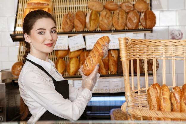 Speziell für dich. porträt einer bäckerin, die frisch gebackenes brot heraushält und freudig lächelt
