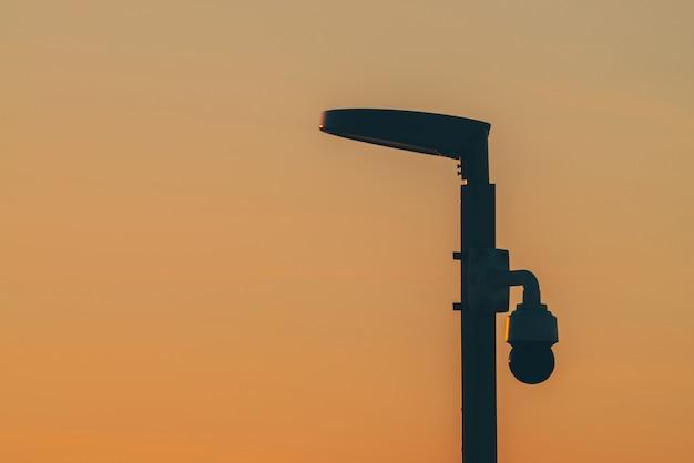Spezielle laterne gegen lichtverschmutzung bei sonnenuntergang nahaufnahme. morgendämmerung mit silhouette der stange mit straßenlaterne und kamera. minimalistische stadtlandschaft vor dem morgengrauen.