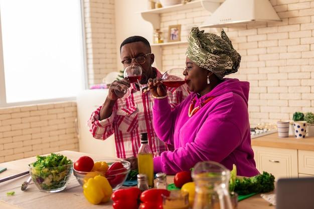 Spezielles getränk. nettes angenehmes paar, das seinen wein genießt, während es in der küche sitzt