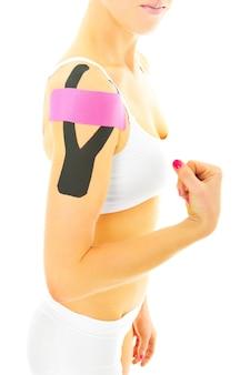 Spezielles physio-tape auf eine verletzte armmuskulatur auf weißem hintergrund