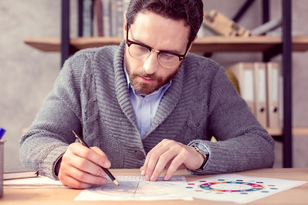 Spezielles schema. ernsthafter kluger astrologe, der seine zeichnung betrachtet, während er eine schicksalsvorhersage macht