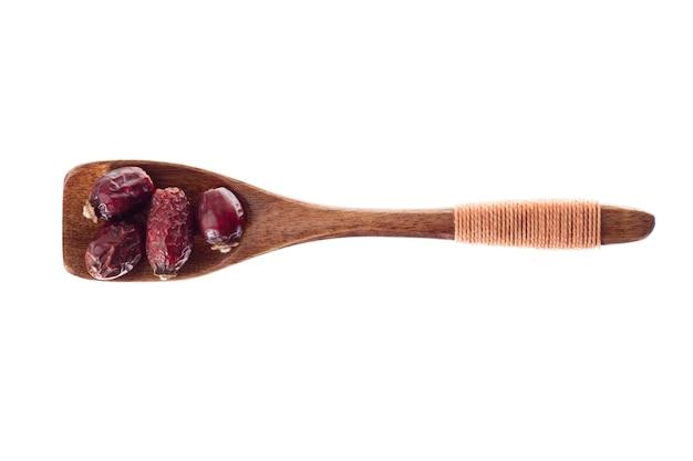 Spice dry berry rose in holzlöffel auf weißem hintergrund