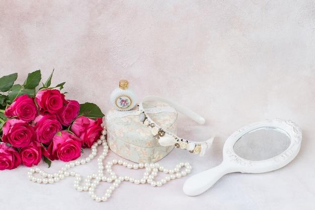 Spiegel, ein strauß rosa rosen, eine schachtel, ein reifen und eine flasche parfüm