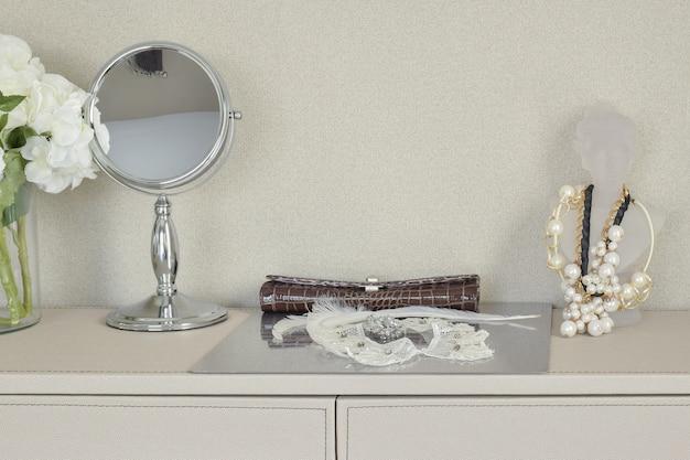 Spiegel, schmuck und make-up auf einem tisch