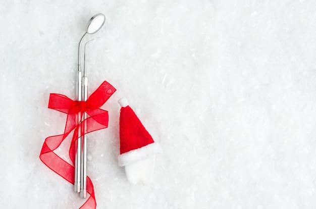 Spiegel und sonde, zahnärztliche instrumente mit rotem band für neujahr, zahn in weihnachtsmütze auf schnee, flach liegen