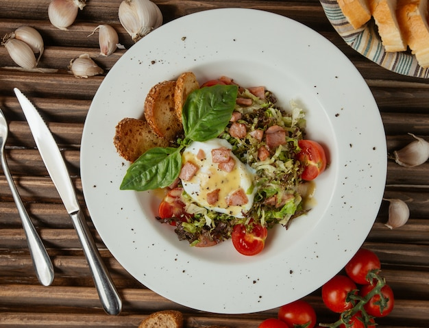 Spiegelei der draufsicht in einer weißen platte mit grünem salat