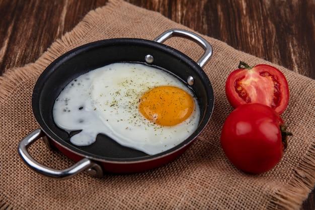 Spiegelei der seitenansicht in einer pfanne mit tomaten auf einer beigen serviette auf einem hölzernen hintergrund