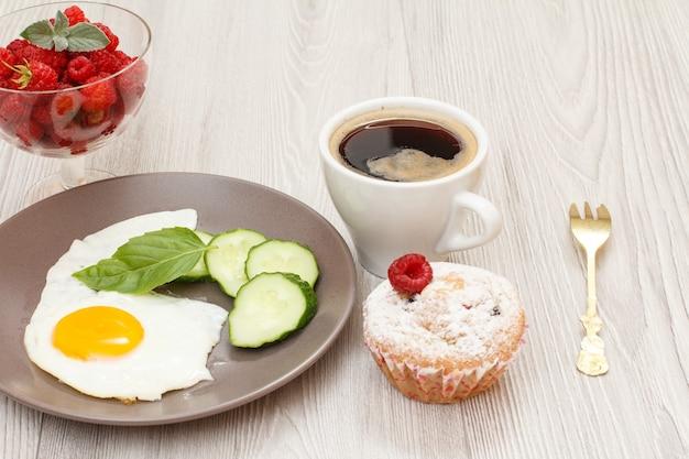 Spiegelei, frisch geschnittene gurke und basilikumblatt, tasse kaffee, muffin und himbeeren.
