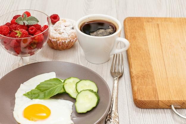 Spiegelei, frisch geschnittene gurken und basilikumblätter, glasschüssel mit frischen himbeeren, tasse kaffee.