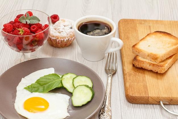 Spiegelei, frische gurken und basilikumblätter, himbeeren, tasse kaffee, gabel, muffin und toast.