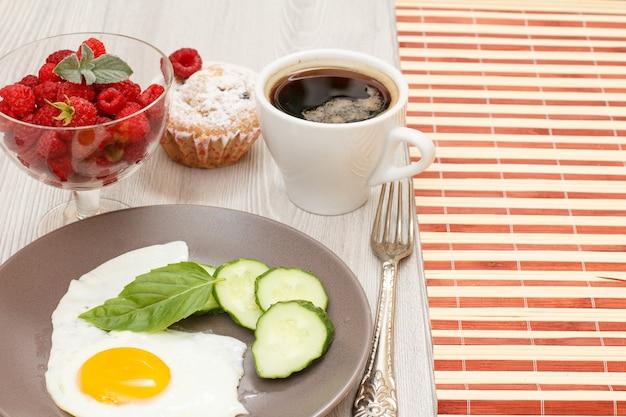 Spiegelei, geschnittene gurke und basilikumblatt, tasse kaffee, muffin und schüssel mit frischen himbeeren