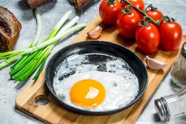 Spiegelei in einer pfanne mit tomaten und frühlingszwiebeln. auf einem rustikalen hintergrund.