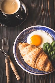 Spiegelei mit croissant und einer tasse kaffee