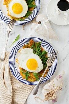 Spiegelei mit kartoffelpuffer, rucola und avocado auf keramikplatte zum frühstück auf weißem holztischhintergrund. draufsicht.