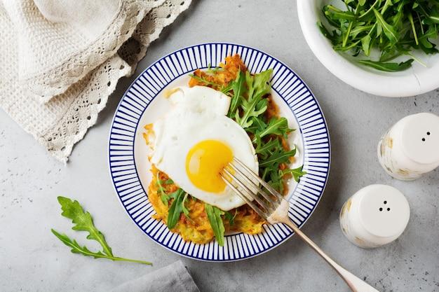 Spiegelei mit kartoffelpuffer, rucola und avocado auf keramikplatte zum frühstück. draufsicht.